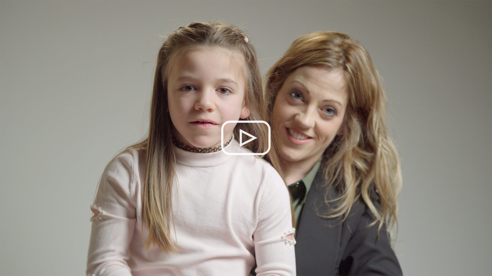 Still image from Turner Syndrome awareness video of Turner Syndrome girl sat on chair looking at camera